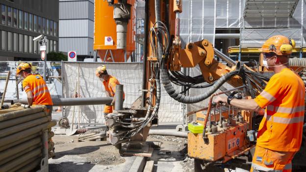 Baustelle mit Betonröhren und drei Arbeitern