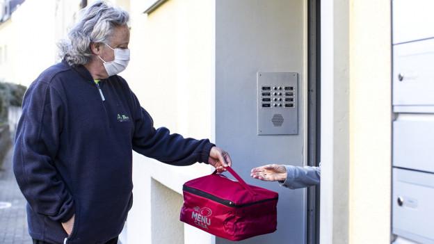 Mann mit Maske übergibt Tasche an Haustüre.