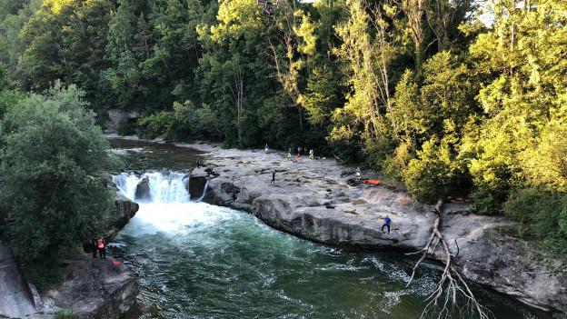 Wasserfall, links und rechts Rettunskräfte am Ufer