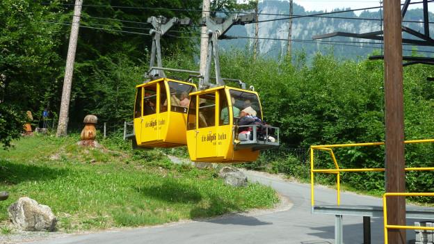 zwei Kabinen fahren aus der Talstation hinaus
