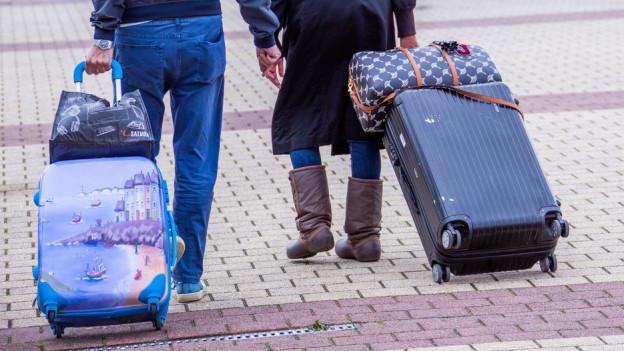 zwei Personen mit Rollkoffer