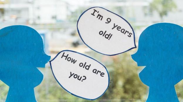 zwei Kinderköpe mit englischen Sprechblasen