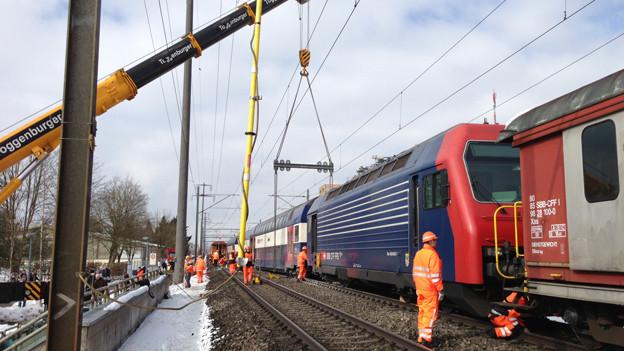 Harte Arbeit: Ein Pneukran hilft den entgleisten Zug zurück auf die Schienen zu stellen.