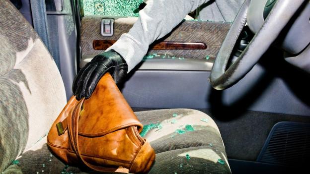 Ein Einbrecher greift nach einer Handtasche im Auto