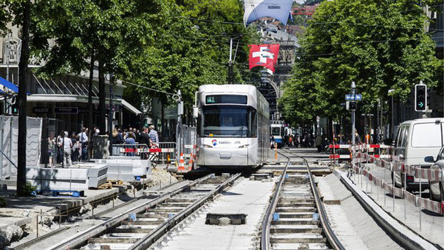 Die Baustelle als Herausforderung für die Arbeiter: Die Trams fahren weiter und die Schaulustigen fotografieren.