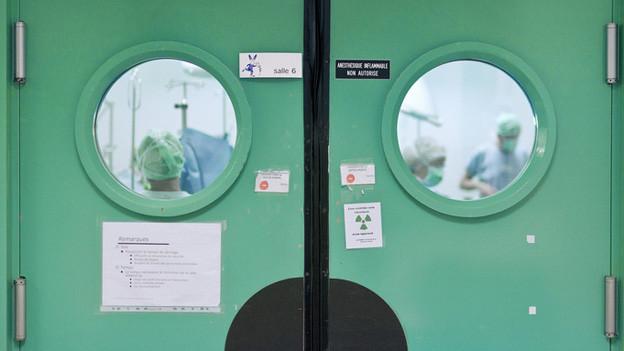 Blick durch die Türfenster in einen Operationssaal des Zürcher Unispitals.