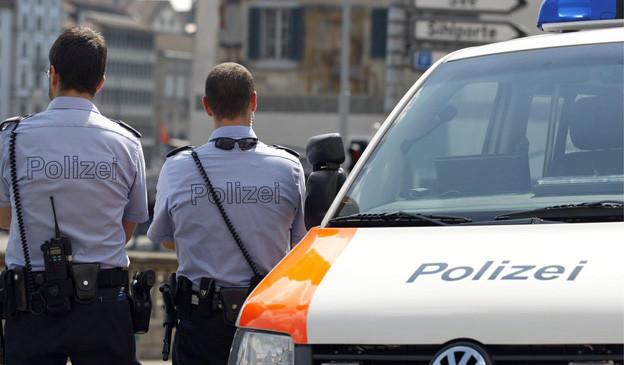 Zwei Mitglieder des Zürcher Polizeicorps vor einem Streifenwagen.