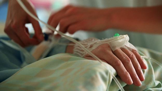 Eine Pflegefachperson verabreicht einer Patientin auf der Bettenstation der Neurochirurgie Schmerzmittel.