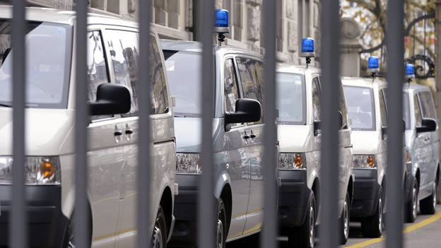 Kastenwagen der Zürcher Stadtpolizei hinter einer Gitterreihe.