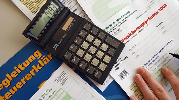 Taschenrechner auf Steuerformularen, drei Finger und ein Stift, bereit um die Formuolare auszufüllen