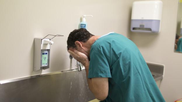 Ein Arzt wäscht sich vor der Operation.