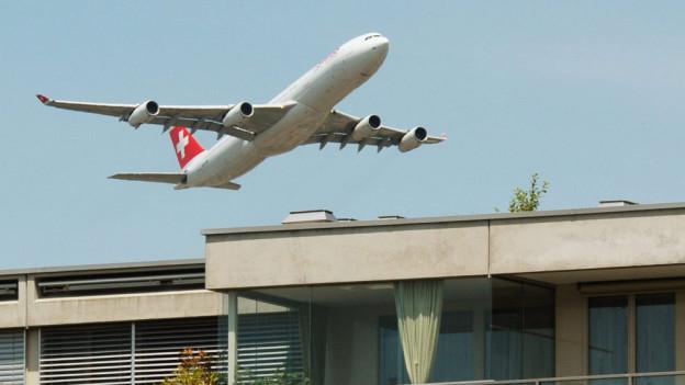 Ein Airbus der Fluggesellschaft Swiss hebt über den Dächern des Glattparks ab.