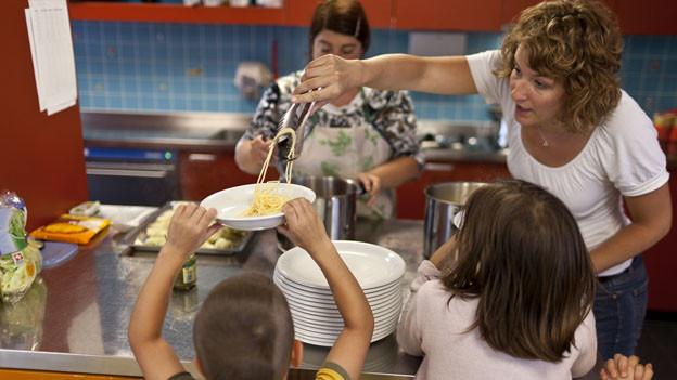 Eine Hortangestellte schöpft den Kindern das Mittagessen.
