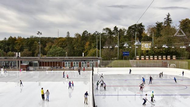 Schlittschuhläufer drehen auf der Eisbahn Dolder ihre Runden und spielen Hockey