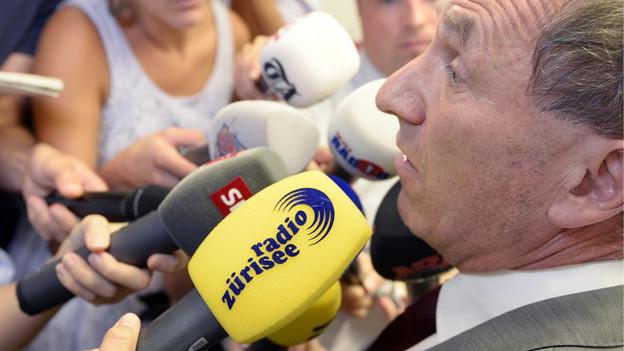 Regierungsrat Martin Graf bedrängt von zahlreichen Radiomikrofonen.