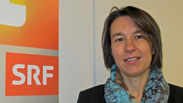 Brustbild von Andrea Gisler neben dem Logo von SRF 1 im Studio des Regionaljournals