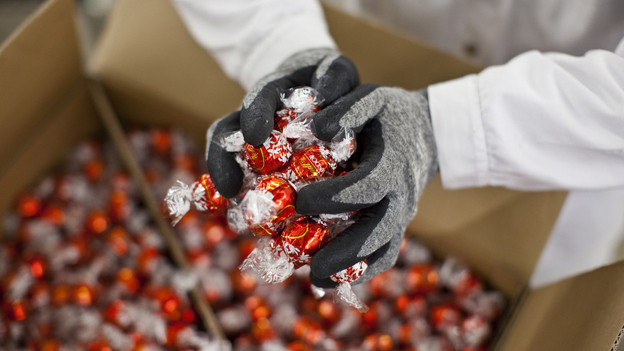 Eine Kiste mit Lindorkugeln, daraus nimmt eine Person eine Handvoll Kugeln.
