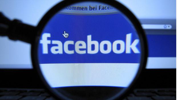 Facebook-Logo durch eine Lupe betrachtet.