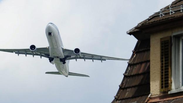 Flugzeugstart über den Hausdächern