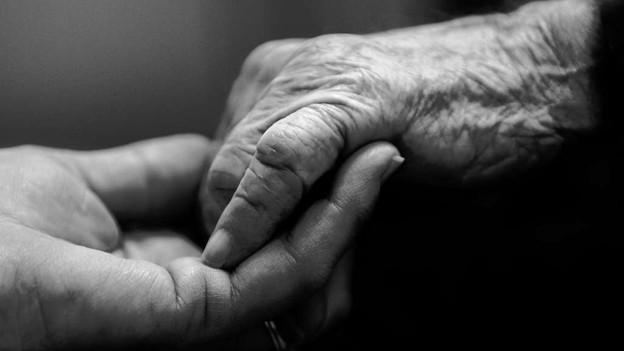 Eine alte Hand greift in eine junge (schwarz-weiss).