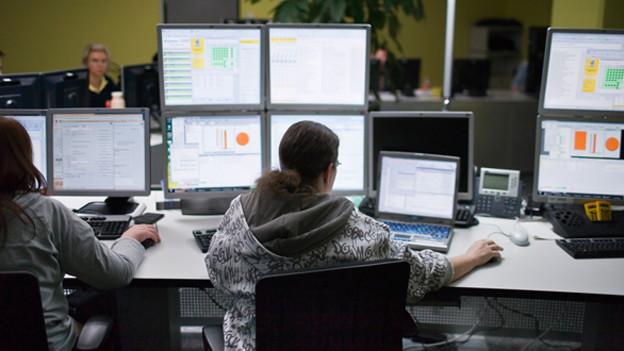 Ein Mann sitzt vor sechs Bildschirmen.