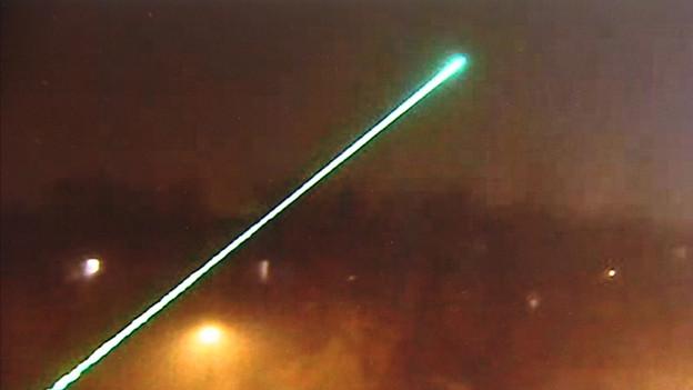 Ein Laserpointer leuchtet in die Nacht.