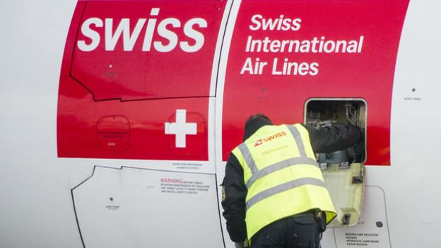Ein Mechaniker vor einem Swiss-Flugzeug.
