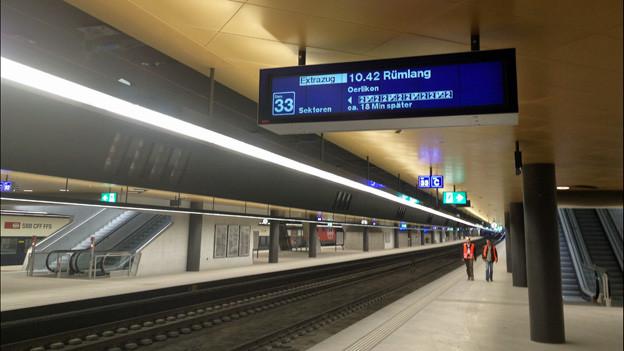 Anzeigetafel, Schienen, Rolltreppen im unterirdischen neuen Bahnhof Löwenstrasse.