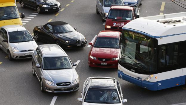 Eine Strasse mit drei Spuren, darauf Autos, quer ein Bus.
