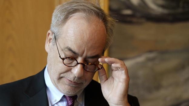 Ein Mann blickt nach unten und fasst sich an die Brille.