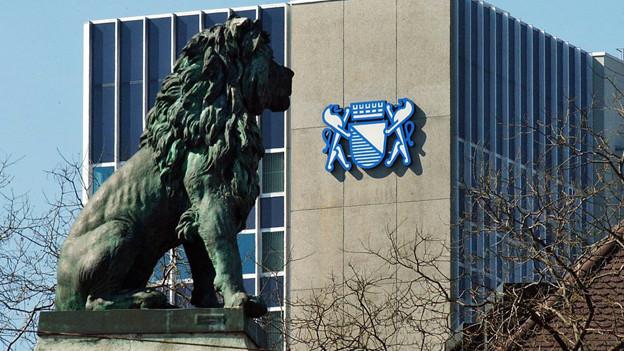 Löwenstatue steht vor Amtsgebäude mit Zürich-Wappen