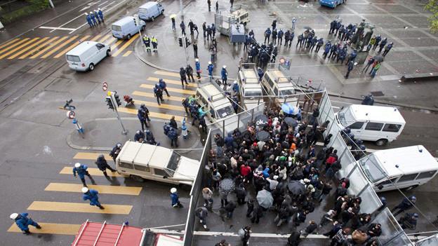 Polizisten kesseln Demonstranten mit Gittern ein