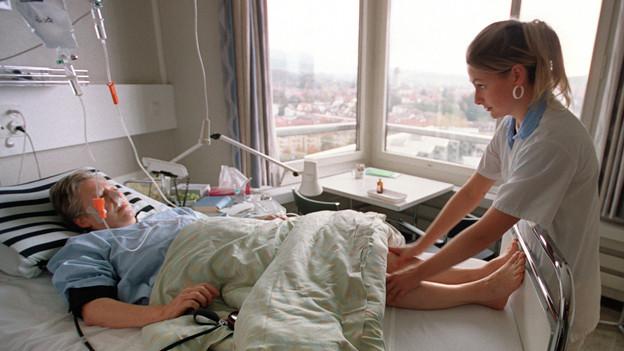 Eine junge Pflegende am Spitalbett eines älteren Patienten.