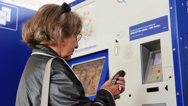 Eine ältere Frau löst ein Billett an einem ZVV-Automaten.