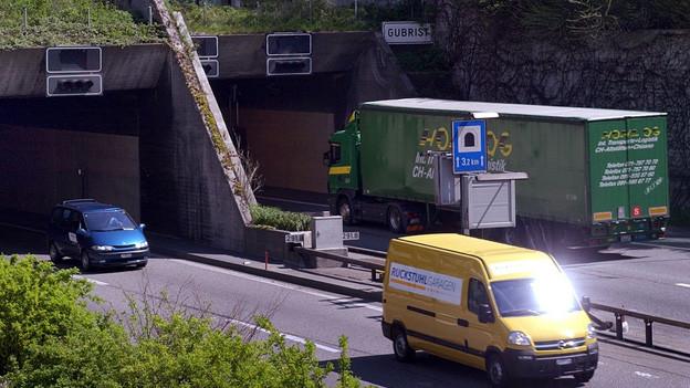 Autos fahren auf Autobahn in den Gubristtunnel bei Weiningen.