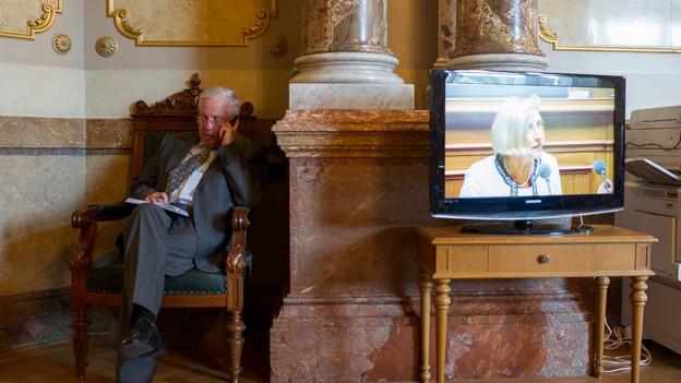 Ein Mann sitzt in einem Stuhl, daneben ein Bildschirm mit der Ratsdebatte.