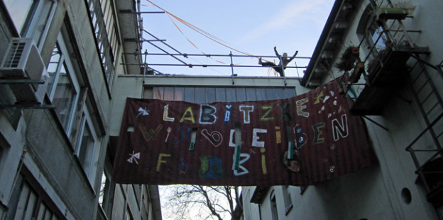 """Ein Transparent mit der Aufschrift """"Labitzke"""" zwischen zwei Häusern."""