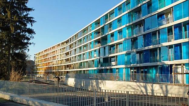 langer Wohnblock mit blauer Glasfassade