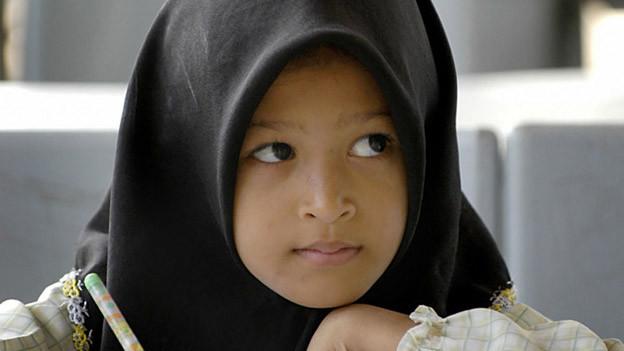 Ein kleines Mädchen mit Kopftuch schreibt in eine Heft.