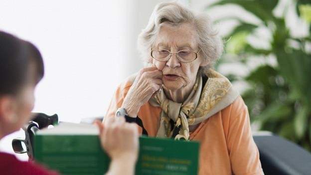 Eine ältere Frau schaut in ein Buch.