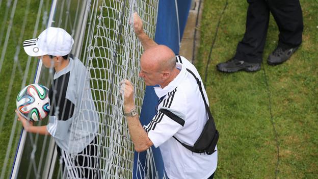 Mann schaut durch Gitter auf Fussballplatz.
