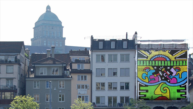 Ein Popart-Bild an einer Hausfassade, im Hintergrund die Universität Zürich.