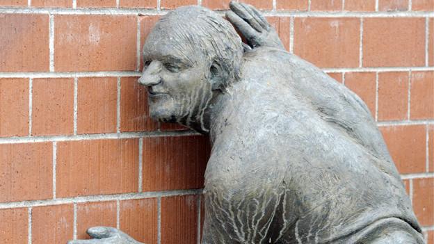 Skulptur eines an einer Mauer lauschenden Manns.