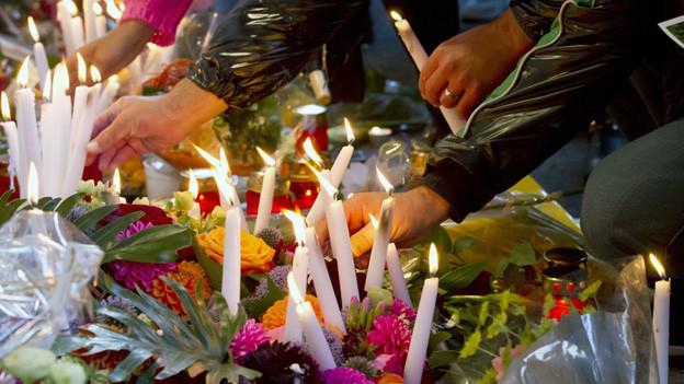 Mit einem Blumenmeer und Kerzen gedachten Hunderte der Tötung vor dem Kaufleuten.