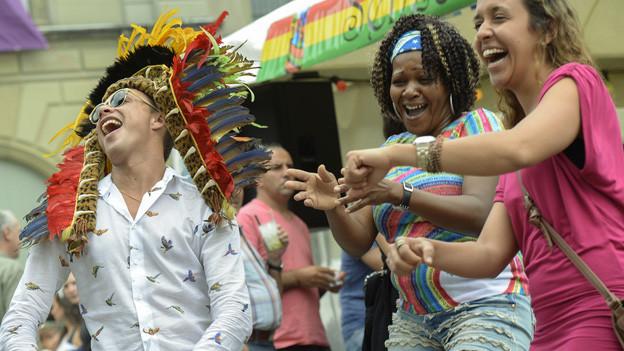Mann mit Indianerfedern auf dem Kopf, zwei Frauen lachen