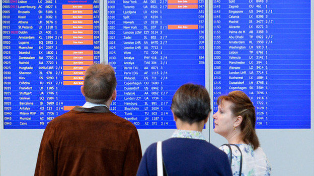 Drei Passagiere vor einer Tafel mit Abflügen.