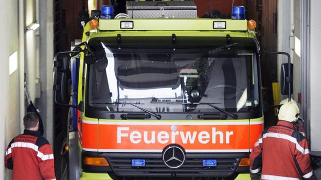 Feuerwehrmänner steigen in ihr Fahrzeug.