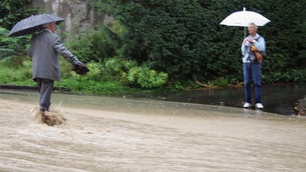 Ein Mann überquert mit den Schuhen in der Hand eine Strasse, die zu einem Bach geworden ist.