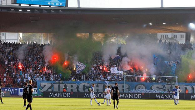 Fussball-Fans verschwinden hinter Rauchschwaden.