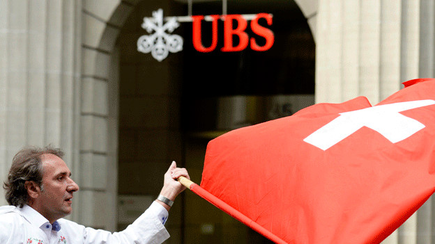 Ein Fahnenschwinger, dahinter das UBS-Logo